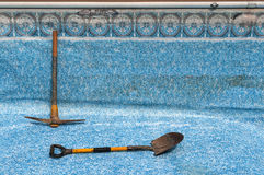 Swimming Pool Repair. View of empty, in-ground swimming pool, with pick and shovel Stock Photos