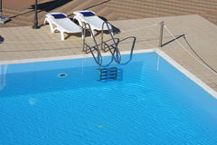 Swimming pool in a resort. Two deckchairs by swimming pool, elevated view Royalty Free Stock Photography