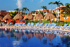 Swimming pool of the resort. Long chairs surrounding the swimming pool to be tan Royalty Free Stock Photos