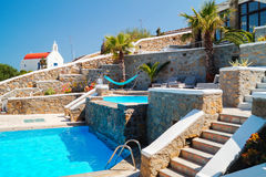 Swimming pool with rock steps and small traditional chapel Royalty Free Stock Photography