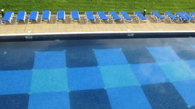 Swimming pool and row of deck chairs stock photos