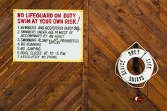 Swimming Pool Rules and Life Preserver. Swimming pool rules posted on wall next to life preserver. Copy space Stock Photography
