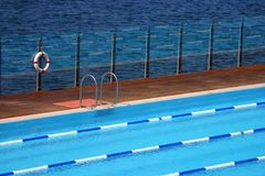 Swimming pool by the sea. With a life-buoy and ladder Royalty Free Stock Photos