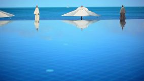 Swimming pool by the sea on background of blue sky. Near beach and white umbrellas. Video shift motion Koh Samui Thailand 1920*1080 stock video footage