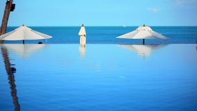 Swimming pool by the sea on background of blue sky. Near beach and white umbrellas. Video shift motion Koh Samui Thailand stock video footage