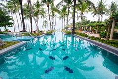 Swimming pool beside the sea with coconut tree. Stock Photos