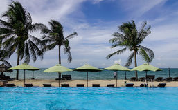 Swimming pool at seaside hotel in Vietnam. Phan Thiet, Vietnam - Mar 26, 2017. Swimming pool with palm trees at sunny day in Phan Thiet, Vietnam. Phan Thiet Royalty Free Stock Image