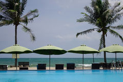 Swimming pool at seaside hotel in Vietnam. Phan Thiet, Vietnam - Mar 26, 2017. Swimming pool with umbrellas in Phan Thiet, Vietnam. Phan Thiet belongs to Binh Stock Photos