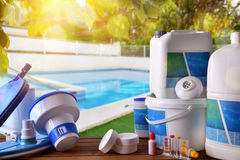 Swimming pool service and equipment with pool background. Swimming pool service and equipment with chemical cleaning products and tools on wood table and pool Royalty Free Stock Images