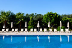 Swimming pool and seven umbrellas Royalty Free Stock Photography