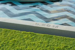 Swimming pool side edge depth show at resort. Stock Photos