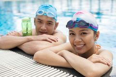 In swimming pool. Smiling Vietnamese couple resting in the swimming pool Stock Image