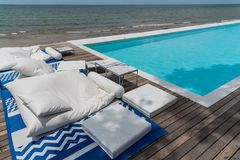 Swimming pool sofa. And the sea Royalty Free Stock Photography