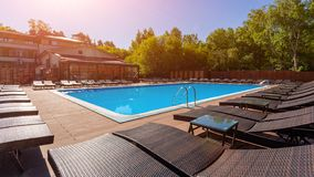 Swimming pool in spa resort . Luxury poolside with sun beds and deck with forest on summer warm day. Tranquil luxury vacation background stock photos