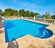 Swimming pool and a spectacular view. Swimming pool with blue water in the yard of a luxury house and a spectacular view Stock Photos