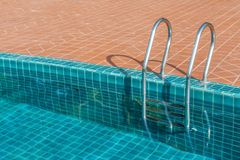 Swimming pool with stainless steel ladder Royalty Free Stock Images