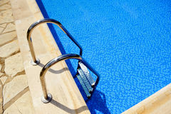 Swimming pool, stainless steel ladder. Stainless steel staircase to exit and enter in the pool royalty free stock images