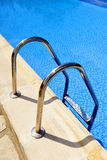 Swimming pool, stainless steel ladder Stock Photos