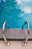 Swimming pool with stair. Metal stairs leading into a swimmingpool Swimming pool with metal stairs leaging and blue relaxing water royalty free stock photography
