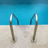 Swimming pool with stair at hotel close up Stock Images