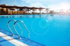 Swimming pool with stair lit by sunlight Stock Photography