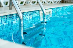 Swimming pool with stair at luxury hotel Stock Images