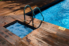 Swimming pool with stair and wooden floor Royalty Free Stock Photos