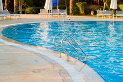 Swimming Pool stairs. Resort swimming Pool stairs with chairs at background royalty free stock image