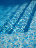 Swimming pool stairs. Blue water and swimming pool stairs Royalty Free Stock Images