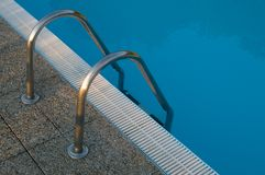 Swimming pool stairs. With handrails royalty free stock images