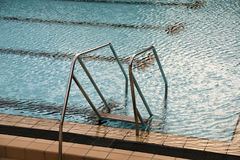Swimming pool stairs. Steel stairs with handrails into the swimming pool royalty free stock images