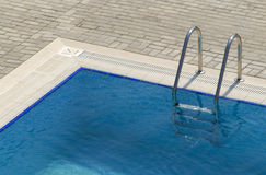 Swimming Pool Steps. Metallic ladder into swimming pool stock image