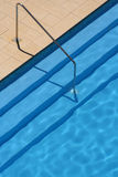 Swimming pool; steps and rail. Looking down into the deep blue of a tranquil swimming pool. Shows steps and stainless steel safety rail Stock Photo