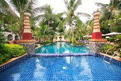 Swimming pool, sun loungers next to the garden and between buildings. Swimming pool with decorative columns at the hotel at the resort. The buildings, sun chairs Royalty Free Stock Photography