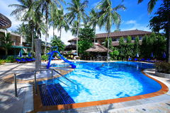 Swimming pool, sun loungers next to the garden and buildings. Swimming pool at the hotel at the resort. The buildings, sun chairs, nice view. A place to relax Royalty Free Stock Images