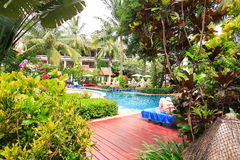 Swimming pool, sun loungers next to the garden and buildings. Swimming pool at the hotel at the resort. The buildings, sun chairs, nice view. A place to relax Stock Image