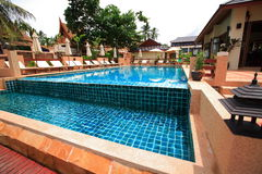 Swimming pool, sun loungers next to the garden and buildings Royalty Free Stock Photo