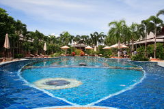Swimming pool, sun loungers next to the garden and bungalow. Swimming pool at the hotel at the resort. The buildings, sun chairs, nice view. A place to relax Royalty Free Stock Images