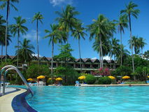 Swimming pool, sun loungers next to the garden and bungalow. Swimming pool at the hotel at the resort. The buildings, sun chairs, nice view. A place to relax Royalty Free Stock Photography
