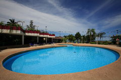 Swimming pool, sun loungers next to the garden and bungalow. Round swimming pool at the hotel at the resort. The buildings bungalow, sun chairs, nice view. A Stock Photography