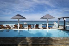 Swimming pool with sun loungers and parasols with beautiful sea views stock photos