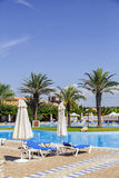 Swimming pool with sun loungers, parasols and palm trees Stock Images