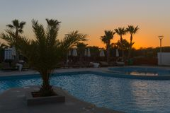 Swimming pool with sun loungers. And umbrellas at sunset stock photos