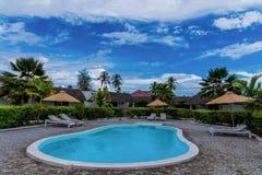 Swimming pool with sun umbrellas and sun beds stock photos