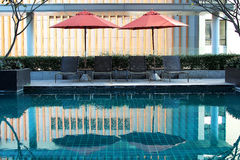 Swimming pool with sunbeds and beach umbrella royalty free stock images