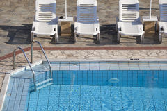 Swimming Pool and Sunbeds Royalty Free Stock Photography
