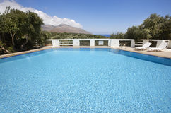 Swimming pool with sunbeds and landscape Royalty Free Stock Photography