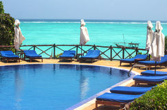 Swimming pool with sunbeds and umbrellas Stock Photos