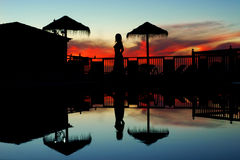 Swimming pool at sunset. View on swimming pool with sky reflection and woman silhouette at sunset Royalty Free Stock Images