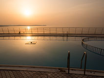 Swimming pool at sunset. Swimming pool near the sea at sunset Royalty Free Stock Image